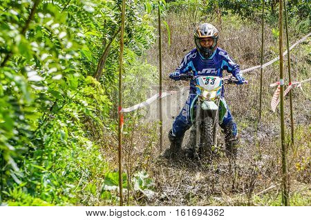 Kundasang,Sabah-Dec 10,2016:Adventurer motocross driver on muddy offroad track during the race at Ranau,Sabah on 10th Dec 2016.Motocross has been an extremely popular motorized sport in Malaysia