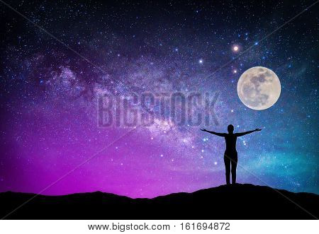 Landscape with Milky way galaxy. Night sky with stars moon and silhouette happy woman on the mountain. (Elements of this moon image furnished by NASA)