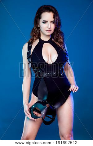beautiful young sexy woman in bodysuit, baldric and black rabbit mask, posing in studio