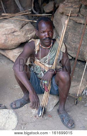 AFRICA, TANZANIA, MAY, 10, 2016 - Hazabe bushman of the hadza tribe preparing arrows for hunting. Hadzabe tribe threatened by extinction in Tanzania, Africa