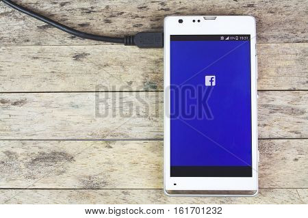 BUNG KAN THAILAND - SEPTEMBER 02 2015: Smart phone and facebook app on screen and charging battery