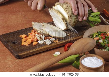 Chef chopping fresh vegetables on kitchen board