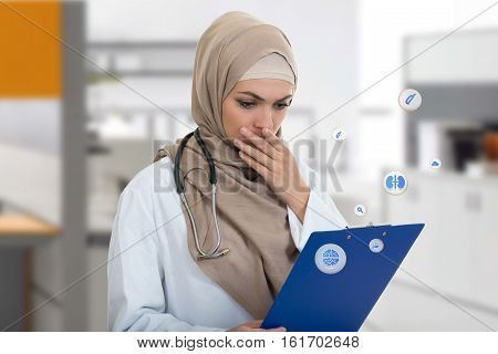 portrait of worried muslim female Medical doctor holding paperclip.
