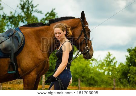 Jockey Young Woman Getting Horse Ready For Ride