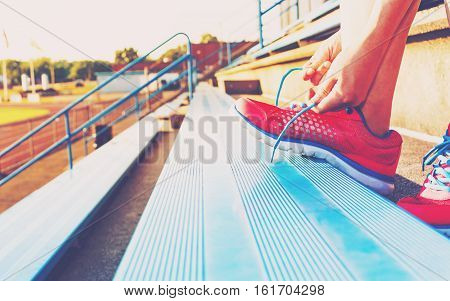 Female Jogger Tying Her Shoes On The Bleachers