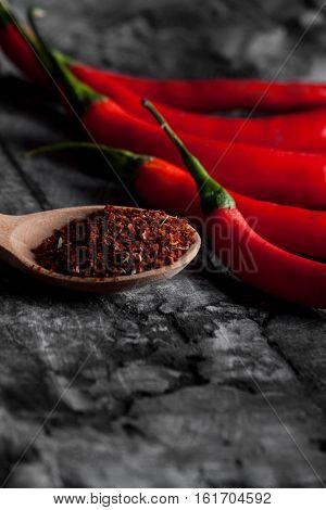 Spoon with seasoning chili and fresh chili on grunge dark background. Food background