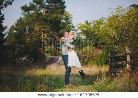 a man kissing woman on background of wooden fence