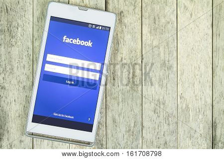 BUNG KAN THAILAND - FEBRUARY 19 2016: smart phone display facebook app on wood background space for caption