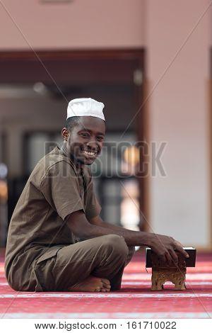 Black African Muslim Man Reading Holy Islamic Book Koran.