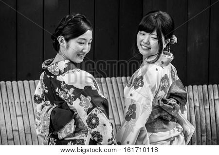 TOKYO, JAPAN - NOVEMBER 11, 2016: Young women wearing traditional japanese kimonos walk on the street of Gion, Kyoto old town, Japan. Kimono is a Japanese traditional garment.