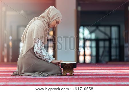 Young muslim woman reading koran in mosque.