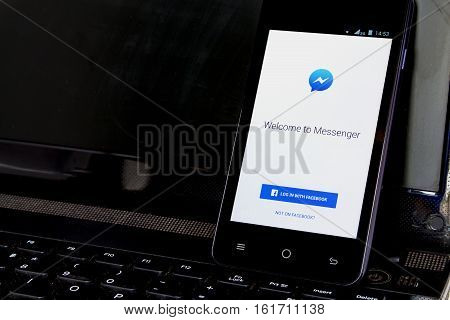 BUNG KAN THAILAND - APRIL 04 2016: smart phone display facebook messenger app on notebook in the office