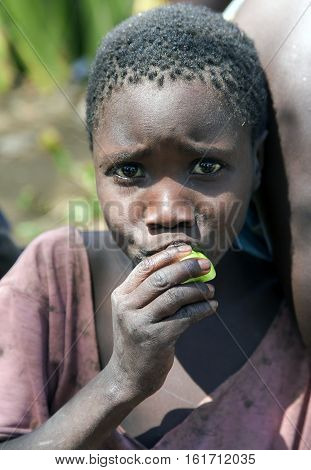 AFRICA, TANZANIA, MAY, 10, 2016 - Close-up portrait  cute african girl of the hadza tribe, that eats fruit in Tanzania, Africa