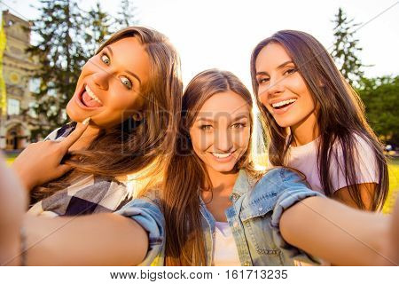 three attractive cheerful best girlfriends with toothy smile making selfie photo and rest on weekend