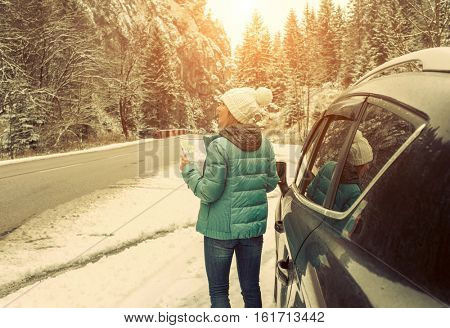 Woman at winter time. Yoyng female with touristic map in her hands sitting in black car at snowly winter day.