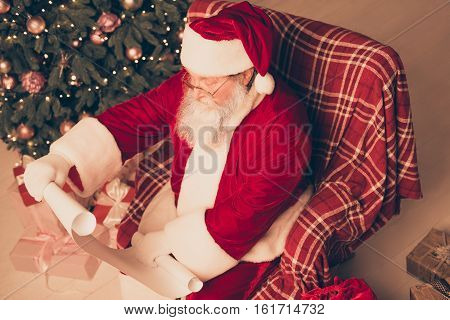Top View Of Old Santa Holding Wishlist From Children