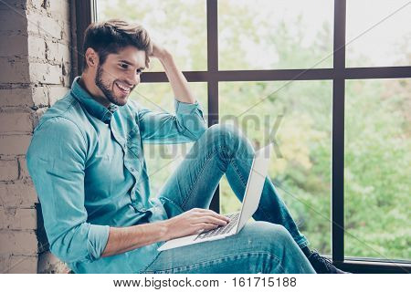 Happy Smiling Man Sitting On Windowsill And Typing On Laptop