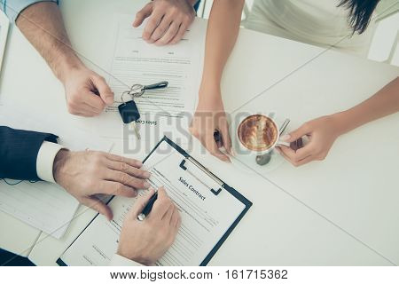 Close Up Of Young Family Signing Contract For Buying House