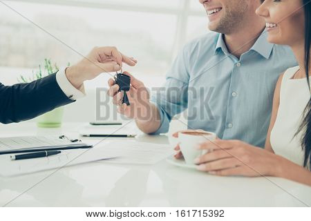 Close Up Photo Of Broker Giving Keys Of New House To Happy Couple