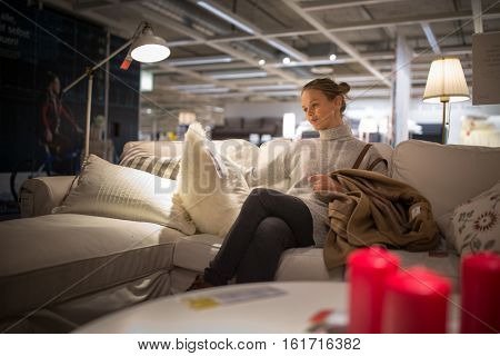Pretty, young woman choosing the right furniture for her apartme