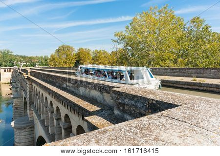 Beziers, France - September 24, 2016; Tourist canal boat Monto Dabalo on Canal Du Midi crosses Orb River by aqueduct in Beziers France
