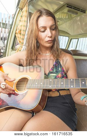 A pretty young woman sits and plays the guitar at the side door of her old classic combi van.