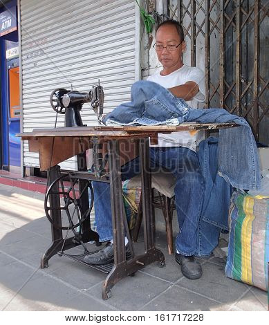 BANGKOK THAILAND - FEBRUARY 10.2015:Tailor sews on the street of Bangkok