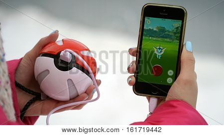 Samara, Russia - December 15, 2016: woman playing pokemon go on his iphone. pokemon go multiplayer game with elements of augmented reality. Catching the Vaporeon pokemon