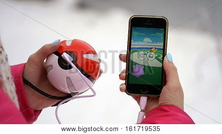 Samara, Russia - December 15, 2016: woman playing pokemon go on his iphone. pokemon go multiplayer game with elements of augmented reality. Ditto versus Pikachu. holidaypikachu with santa hat for christmas event