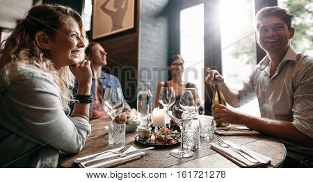 Group of friends enjoying an evening meal with wine at a restaurant. Happy young man and woman having dinner in a restaurant.