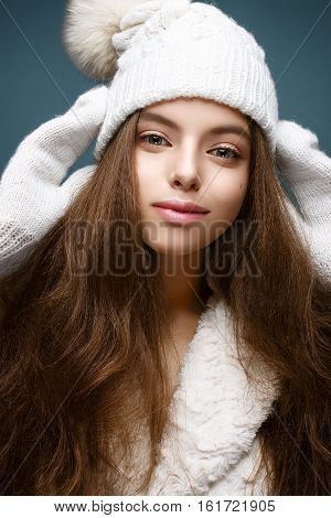 Beautiful girl in a white knitted hat with fur pompom. Model with gentle nude make-up. Cozy winter picture. Beautiful face.