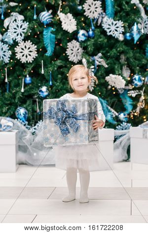 Portrait of happy funny smiling blonde Caucasian baby girl toddler in white dress clothes with gift present box by New Year tree lifestyle Christmas holiday concept