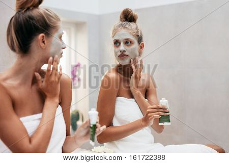 Young woman with cosmetic mask on face in bathroom. Female applying face mask infront of mirror.