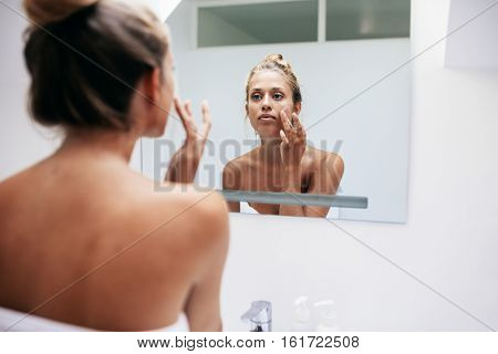Woman In Bathroom Applying Cream On Face