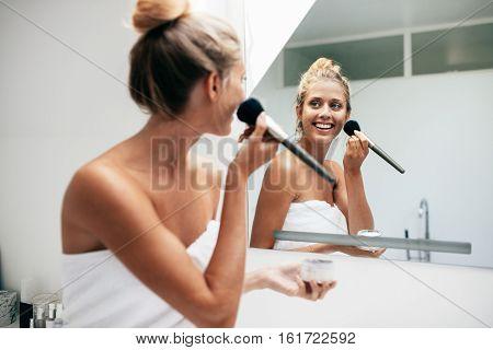 Beautiful Young Woman Applying Makeup In Bathroom