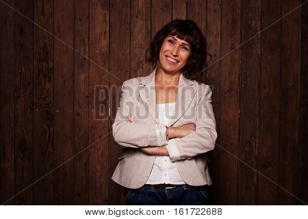 Beautiful smiling chestnut female standing against the brown wooden background, wearing dark blue jeans, white blouse and light blazer. Lady folding arms, having riant eyes and cute smile