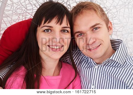 Close-up portrait of happy married couple. Sitting closely together. Caucasian couple. Enjoying time  together. Sitting in a swinging hanging chair