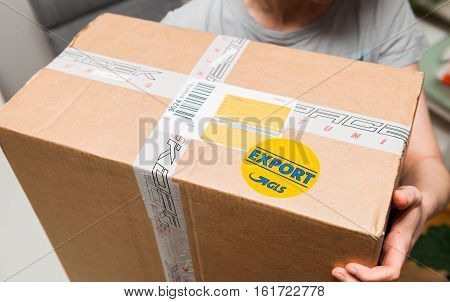 PARIS FRANCE - DEC 7 2016: View from above of woman unpacking parcel from GLS logistics with the sticker GLS Export