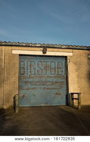 A yellow brick building with a closed blue door in a loading bay.