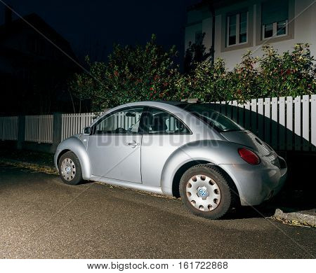 STRASBOURG FRANCE - 26 NOV 2016: Modern silver Volkswagen Beetle car on the street of Strasbourg France with beautiful houses in the background at night