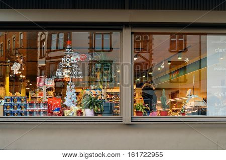 STRASBOURG FRANCE - DEC 1 2016: Carrefour supermarket at the evening with Christmas tree sticker on the windows and customers buying diverse food and non-food products. Carrefour is the largest chain of stores in France
