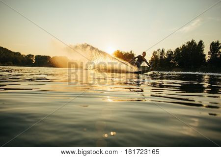 Wakeboarder moving fast in splashes of water at sunset. Man water skiing on a lake.