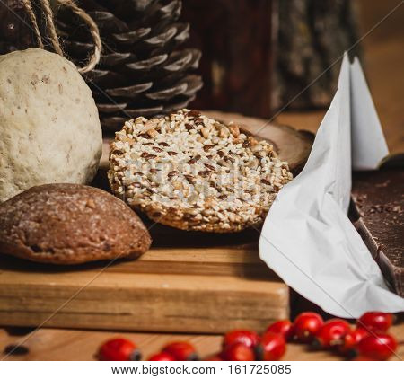 sesame cookies with gingerbread on the background, chocolate pieces and rosehip berries on a wooden table