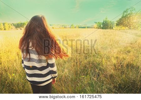 teen girl with long brown loose hair stay back on the summer field on sunny day