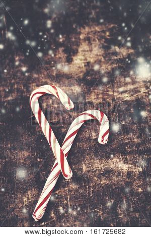 Christmas Card with striped hard candy cane over wooden background. Christmas candy Closeup. Red and white colours with falling snow