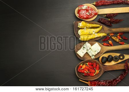 Ingredients for spicy barbecue on the wooden spoon. Dried chillies and spicy peppers filled with cheese. Delicacy suitable for grilled meats. Chillies and cheese. Advertising on spicy delicacies.