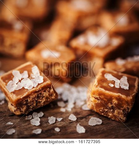 Golden Salted caramel pieces and sea salt macro on wooden board.