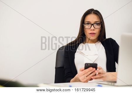 Closeup portrait young, shocked business woman, looking at cell phone seeing bad text message, email, isolated indoors office background. Negative emotions, facial expressions.