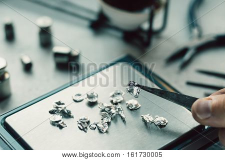 Jewelry tools. Jewellery. Goldsmith workplace workspace on light background. Hand craft. Workshop. Manufacturing. Weigh-scales with granules of metal silver and platinum. Closeup. Toned poster