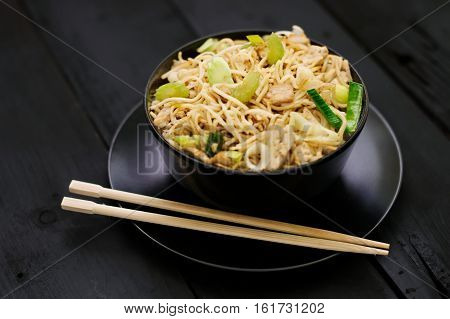 Asian food Chow Mein ramen noodles with vegetables and tofu in black bowl and plate with chopsticks on dark wood surface. Concept of asian food. Concept of chinese food.